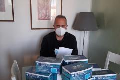 Un volontario imbusta le mascherine prima della consegna a domicilio